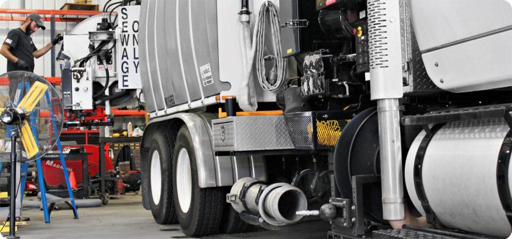 Technician repairs sewer vacuum truck